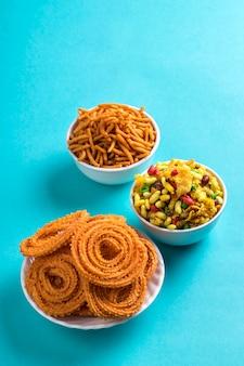 Snack indien: chakli, chakali ou murukku et besan (farine de gram) sev et chivada ou chiwada sur fond bleu. diwali food