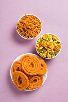 Snack indien: chakli, chakali ou murukku et besan (farine de gram) sev et chivada ou chiwada sur fond rose. diwali food