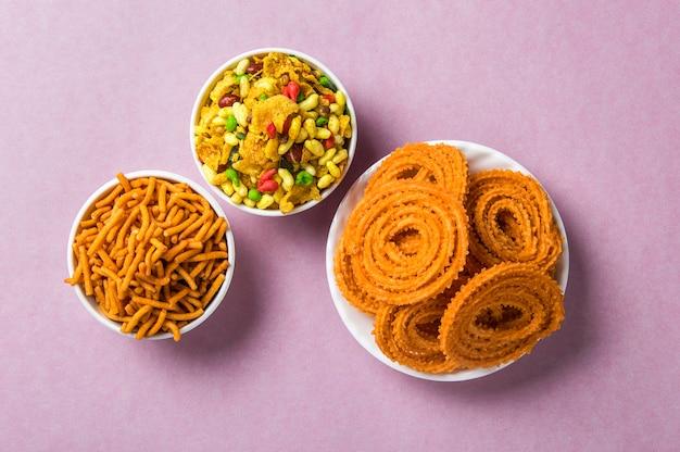 Snack indien: chakli, chakali ou murukku et besan (farine de gram) sev et chivada ou chiwada sur une surface rose. diwali food