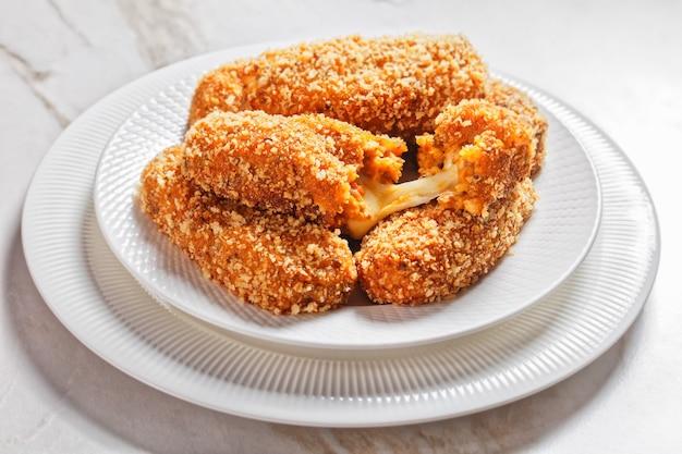 Snack italien suppli al telefono ou croquettes de riz farcies de fromage mozzarella servies sur une assiette blanche sur fond de marbre clair, vue de dessus, gros plan
