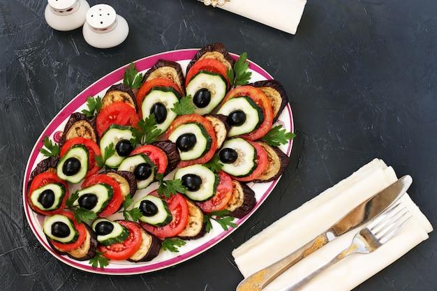 Snack peacock's queue d'aubergines, tomates, concombres et olives est situé sur un fond sombre