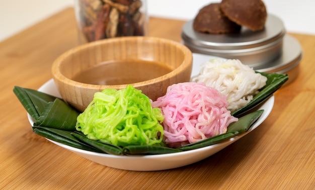 Snack putu mayang du javanais à base de farine de riz mangée avec du lait de coco et du sucre de palme