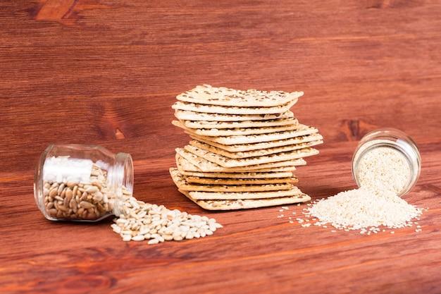 Snack santé céréales multigrains croquantes graine de lin, sésame, barre de pain protéiné aux graines de tournesol et graines de tournesol et de sésame dans un pot.