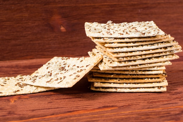 Snack santé céréales multigrains croquantes graines de lin, sésame, barre de pain protéiné aux graines de tournesol.