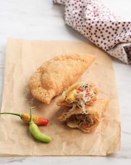 Snack traditionnel indonésien ou jajan pasar: pastel goreng ou poche de pâtisserie frite remplie de légumes, d'œufs durs, de nouilles de verre et d'épices enveloppées dans une pâte feuilletée et frites jusqu'à ce qu'elles soient croustillantes