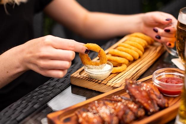 Snacks à la bière assortis, restauration rapide. ailes de barbecue et apéritif de rondelles d'oignon, fromage affiné, viandes, cornichons, frites, nachos, pistaches, frites et saucisses avec chope de bière.
