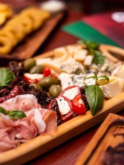 Snacks à la bière assortis, restauration rapide. apéritif au fromage bleu, pastrami de charcuterie, cornichons, frites, nachos, pistaches, frites et saucisses avec chope de bière.