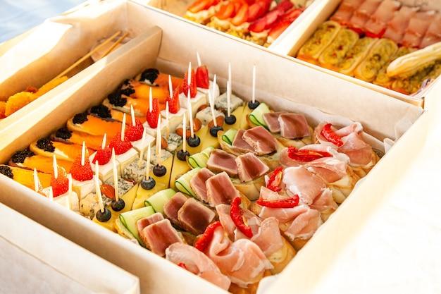 Snacks gourmands en carton avec sandwichs, éclairs, bruschetta avec charcuterie, fromage et fruits de mer pour buffet traiteur et fête.