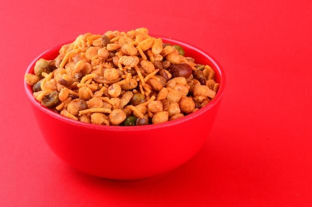 Snacks indiens: mélange (noix grillées avec sel poivre masala, légumineuses, channa masala dal, pois verts) dans un bol rouge