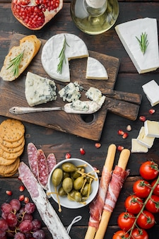 Snacks italiens, fromage à la viande, ensemble d'herbes, sur fond de bois foncé, vue de dessus