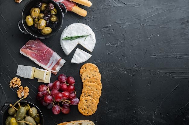 Snacks italiens, fromage à la viande, ensemble d'herbes, sur fond noir
