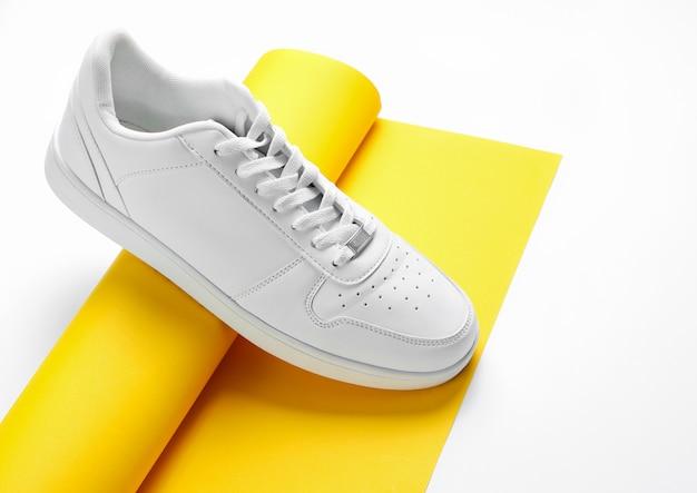Sneaker blanche sur rouleau de papier jaune enroulé.