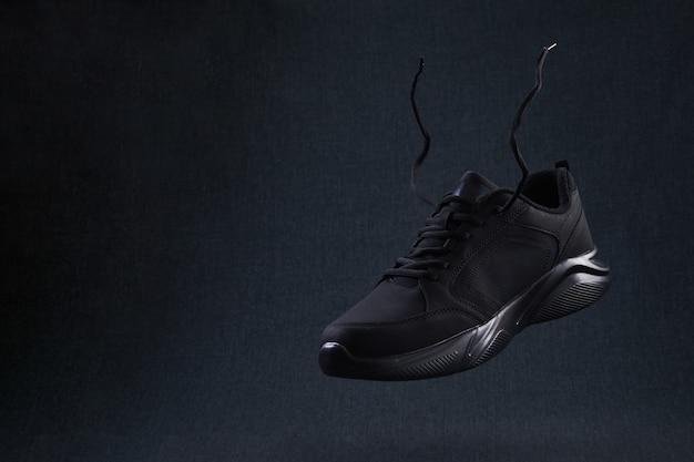 Sneaker mode noir sans marque avec des lacets volant sur fond sombre. les chaussures de sport noires lévitent dans les airs.