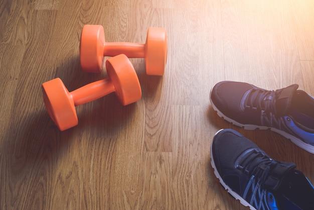 Sneakers et haltères fitness sur bois