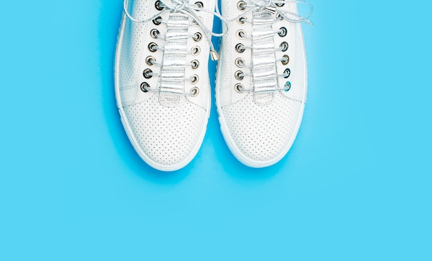 Sneakers isolés sur fond bleu, mode. chaussures blanches.