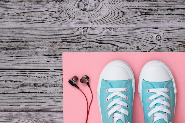 Sneakers sur un tapis de corail et des écouteurs sur un plancher en bois.