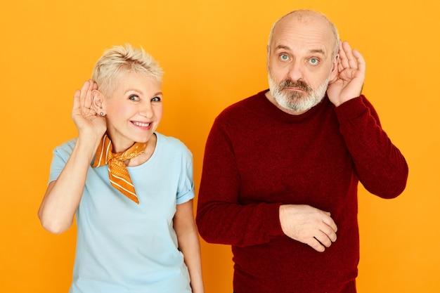 Snoopy senior man avec une barbe grise épaisse posant isolé avec sa jolie femme blonde curieuse tenant la main à l'oreille, essayant d'entendre une conversation privée ou des nouvelles curieuses secrètes, écoute clandestine