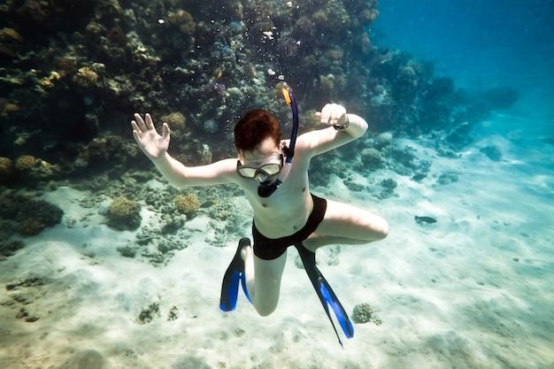 Snorkeler plongée le long du corail du cerveau