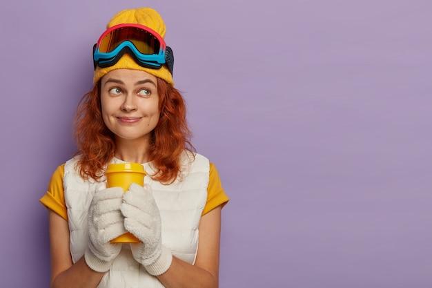 Snowboarder actif aux cheveux roux, a une expression pensive, tient du café à emporter, porte des gants blancs, des lunettes de ski, concentré de côté sur un fond violet.