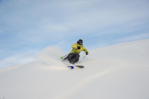 Snowboarder actif glissant sur la colline enneigée