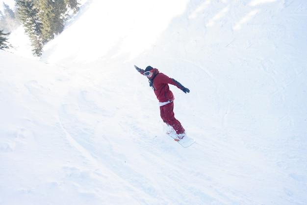 Snowboarder actif sautant dans les montagnes par une journée ensoleillée