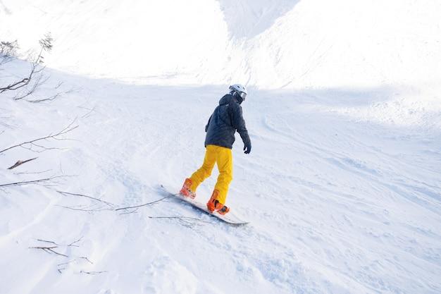 Snowboarder actif sautant dans les montagnes par une journée ensoleillée.