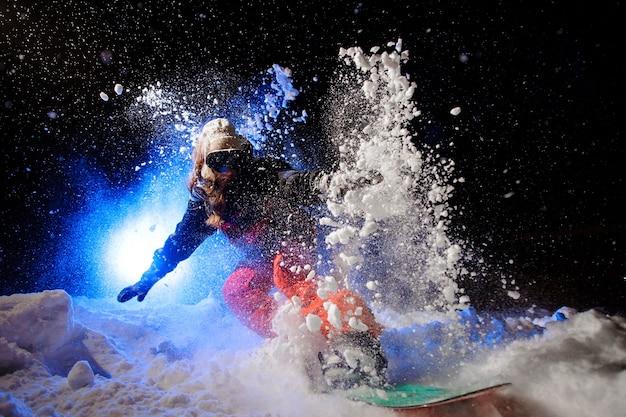 Snowboarder active vêtue d'un vêtement de sport orange à cheval sur le versant de la montagne la nuit sous la lumière bleue
