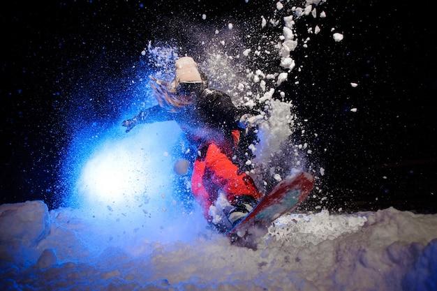 Snowboarder active vêtue d'un vêtement de sport orange sautant sur la pente de la montagne dans la nuit sous la lumière bleue