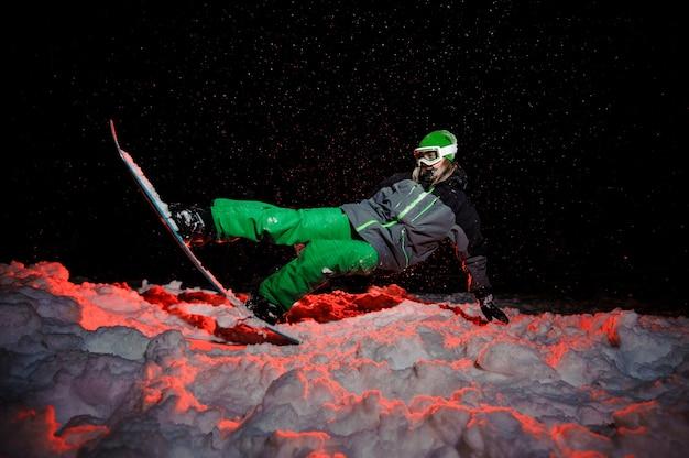 Snowboarder active vêtue d'un vêtement de sport vert à cheval sur la colline de la montagne dans la nuit sous la lumière rouge