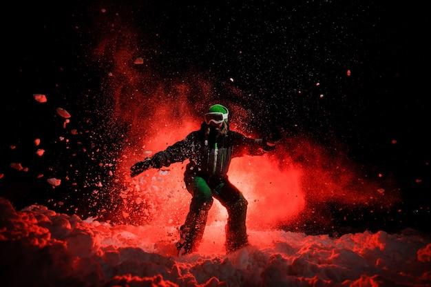 Snowboarder active vêtue d'un vêtement de sport vert équitation sous la neige la nuit sous la lumière rouge