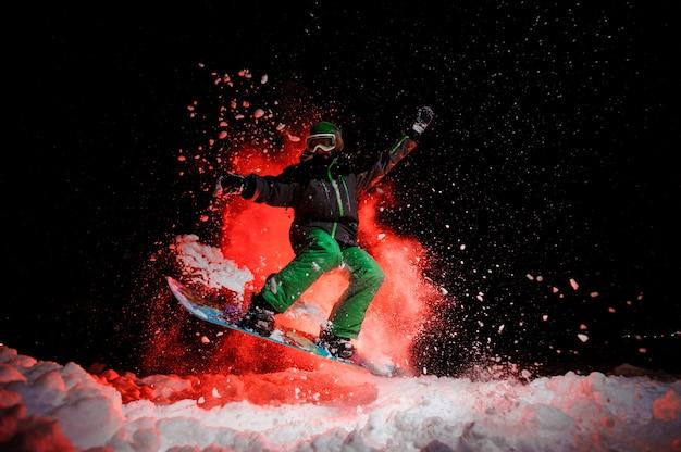 Snowboarder active vêtue d'un vêtement de sport vert sautant sous la neige la nuit sous la lumière rouge