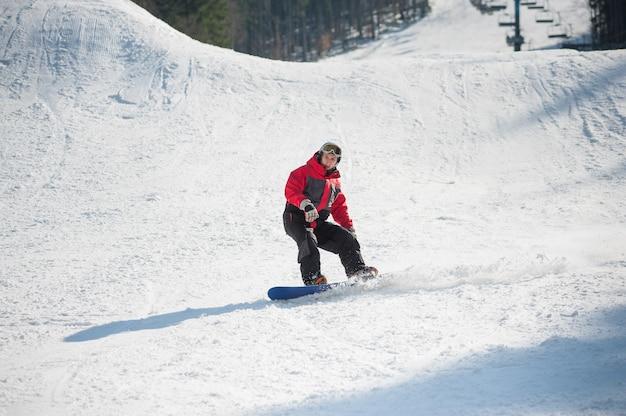 Snowboarder chevauche sur la neige fraîche après le saut