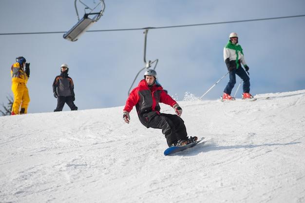Le snowboarder commence la descente sur piste en haut de la piste