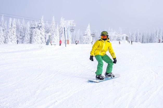 Snowboarder dans un costume jaune et vert en descendant la pente avec une remontée mécanique dans le