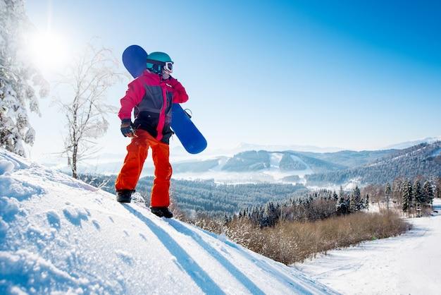 Snowboarder debout au sommet de la montagne à la recherche de repos après avoir roulé