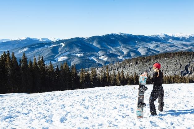Snowboarder debout avec chaîne de montagnes en arrière-plan
