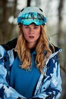 Snowboarder femme en costume lumineux dans des lunettes de sport est titulaire d'un snowboard. sports extrêmes. loisirs.