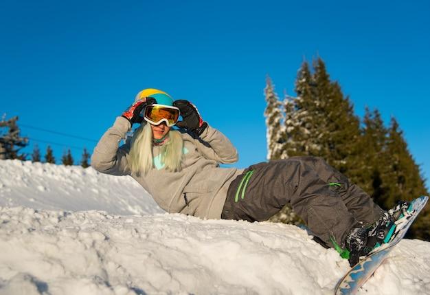 Snowboarder femme sur pente dans les montagnes