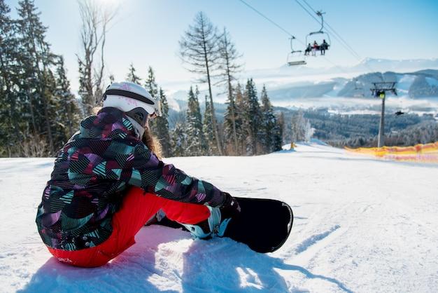 Snowboarder femme reposant sur la piste de ski sous les remontées mécaniques avec un beau paysage de montagnes et de forêts par une journée ensoleillée