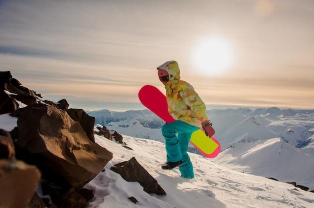 Snowboarder femme sportswear avec un snowboard rose marchant sur les sommets des montagnes
