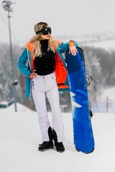 Snowboarder femme en vêtements de sport posant dans des lunettes de soleil avec un snowboard
