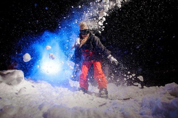 Snowboarder femme vêtue d'un vêtement de sport vert debout sur le versant de la montagne dans la nuit sous la lumière bleue