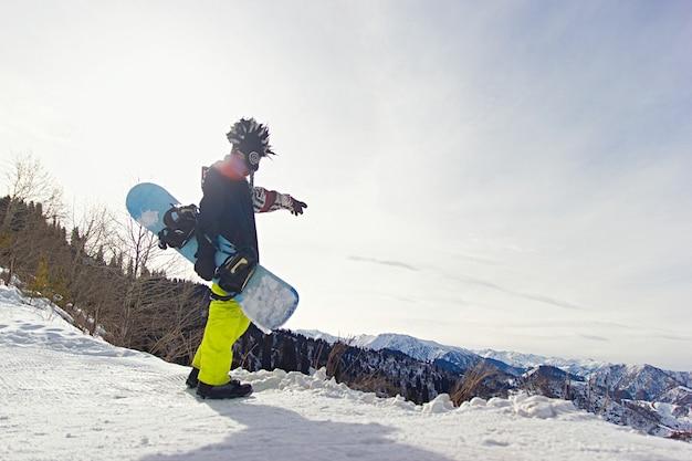 Le snowboarder freerider dans les montagnes se prépare à descendre sur fond de montagnes enneigées