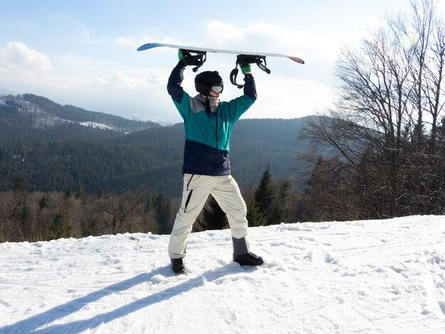 Snowboarder heureux d'avoir pu descendre le flanc de la montagne