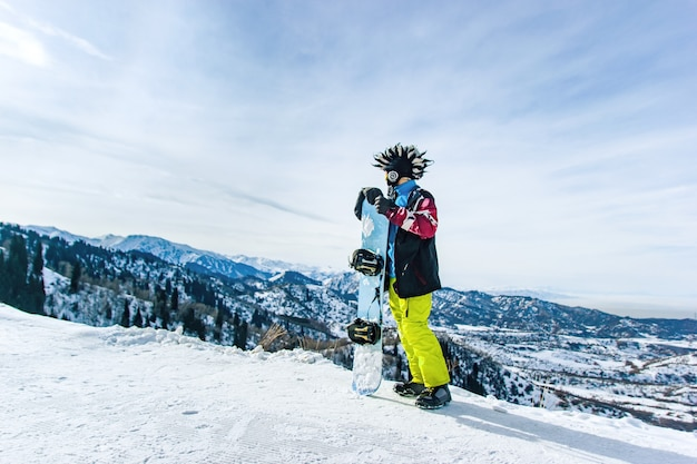 Snowboarder heureux barbu dans un masque de ski avec des lunettes et un grand chapeau mohawk de fourrure sur un fond de ciel