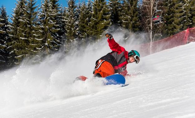 Snowboarder homme appréciant le ski dans les montagnes sur une journée d'hiver ensoleillée