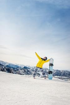 Snowboarder de jeune femme dans une veste jaune et un casque noir sur le fond des montagnes enneigées