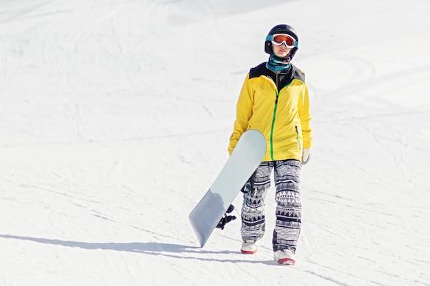Snowboarder jeune femme marchant sur une piste de ski tenant son snowboard shes looking at camera