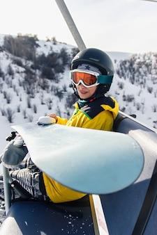 Snowboarder de jeune femme s'asseyant sur l'ascenseur de ski tenant son snowboard, elle regarde la caméra