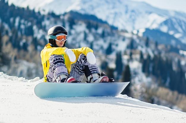 Snowboarder de jeune femme s'asseyant dans la neige et explorant la pente avant la descente